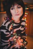 Beautiful young woman with christmas lights. Beautiful young woman holding christmas lights in her hands royalty free stock photos