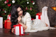 Beautiful young woman, Christmas tree and gift box. stock images