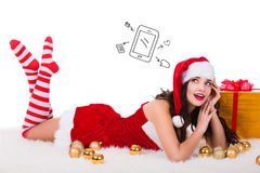 Beautiful young woman in Christmas wear dreaming about tablet PC as gift. Isolated on white background. Royalty Free Stock Images