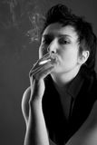 Beautiful young woman with a cigarette. And smoke Stock Images