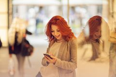 Beautiful young woman in the city, mall is busy with her mobile phone, talking, smiling stock photos