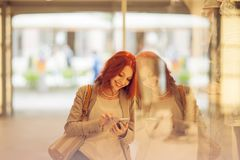 Beautiful young woman in the city, mall with cell phone, mobile phone, happy shopping tour. Autumn mood colors Stock Images