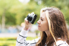 Beautiful young woman with classic camera in the street. Stock Photography