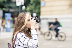 Beautiful young woman with classic camera in the street. Stock Photo