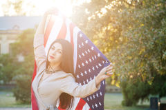 Beautiful young woman with classic dress holding american flag in the park. fashion model holding us smiling and looking at camera Stock Photo