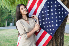 Beautiful young woman with classic dress near american flag in the park. fashion model holding us smiling and looking at camera. u Royalty Free Stock Images
