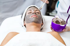 Beautiful young woman with clay facial mask in beauty spa. Detox stock photos