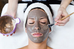 Beautiful young woman with clay facial mask in beauty spa. Detox royalty free stock photos