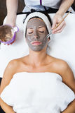 Beautiful young woman with clay facial mask in beauty spa. Detox royalty free stock images