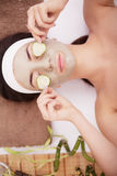 Beautiful young Woman in clay mud mask on face covering eyes with slices cucumber. Stock Images