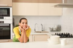 Beautiful young woman with clean dishes and cups at table. In kitchen royalty free stock image