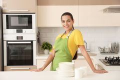 Beautiful young woman with clean dishes and cups at table. In kitchen royalty free stock photo
