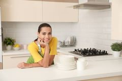 Beautiful young woman with clean dishes and cups. At table in kitchen stock photography