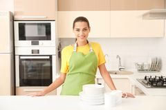 Beautiful young woman with clean dishes and cups at table. In kitchen stock photos
