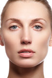 Beautiful young woman with clean fresh skin close-up. Beautiful woman face close up studio on white. Young woman with cosmetic cre Royalty Free Stock Images