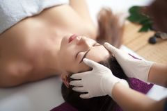 Beautiful young girl having face massage in spa salon Stock Photo