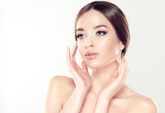 Beautiful young woman with clean fresh skin. Cosmetic and cosmetology. Beautiful young woman with clean fresh skin, bare sholders and elegant gesture. Close up Royalty Free Stock Photo