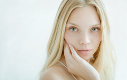 Beautiful young woman with clean fresh skin. On light background Royalty Free Stock Image