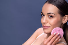 Beautiful young woman with clean fresh skin touch own face. Cosmetology, beauty and spa. Smiling young girl cleaning her face wit royalty free stock image