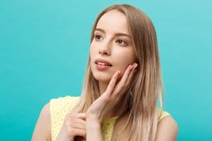 Beautiful young woman with clean perfect skin. Portrait of beauty model touching her face. Spa, skincare and wellness. Close up, blue background, copyspace stock photography