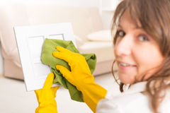 Beautiful young woman cleaning frame Royalty Free Stock Image