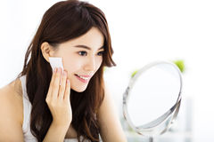 Beautiful  young woman cleaning her face with cotton Stock Photography