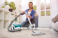 Beautiful young woman cleaning with vacuum cleaner Stock Photo