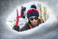 Beautiful young woman cleaning windshield of snow Stock Photos