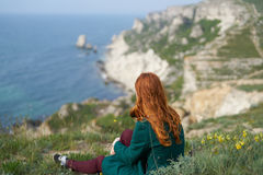 Beautiful young woman on a cliff of a mountain near the sea Stock Photos