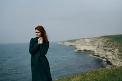 Beautiful young woman on a cliff of a mountain near the sea Stock Photo