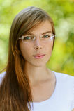 Beautiful young woman close up. Portrait of beautiful young woman with glasses close up, against green of summer park Stock Photos