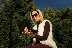 Beautiful young woman close up. Blonde girl is sitting on steps outside an office, holding a tablet. Female with notebook. Royalty Free Stock Image