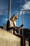 Beautiful young woman close up. Blonde girl is sitting on steps outside an office, holding a tablet. Female with notebook. Royalty Free Stock Photo