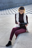 Beautiful young woman close up. Blonde girl is sitting on steps outside an office, holding a tablet. Female with notebook. Royalty Free Stock Photos