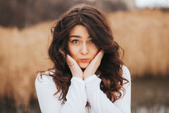 Beautiful young woman close-up in orange sweater, against green of summer park. Stock Photography