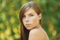 Beautiful young woman close up. Portrait of sad beautiful young woman close up, against green of summer park Stock Photo