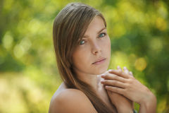 Beautiful young woman close up. Portrait of sad beautiful young woman close up, against green of summer park Royalty Free Stock Photo