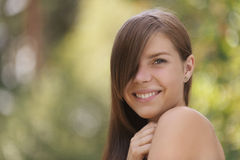 Beautiful young woman close up. Portrait of smiling beautiful young woman close up, against green of summer park Royalty Free Stock Images