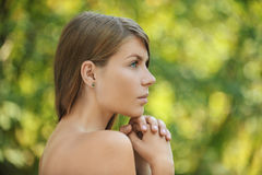 Beautiful young woman close up in profile. Portrait of beautiful young woman close up in profile, against green of summer park Royalty Free Stock Photos