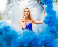 Beautiful young woman in a cloud of a bright blue smoke Stock Photos