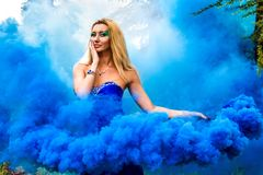 Beautiful young woman in a cloud of a bright blue smoke Royalty Free Stock Photos