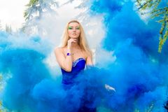 Beautiful young woman in a cloud of a bright blue smoke Stock Image