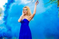 Beautiful young woman in a cloud of a bright blue smoke Royalty Free Stock Image