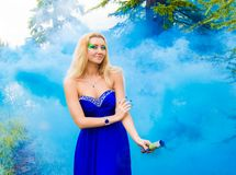 Beautiful young woman in a cloud of a bright blue smoke Royalty Free Stock Images