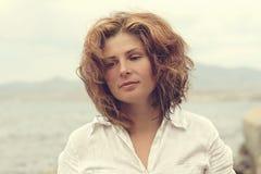 Beautiful young woman on a coast sea. Beautiful young woman in white shirt on a coast sea Royalty Free Stock Photography