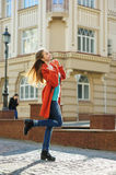 Beautiful young woman in coat walking down the street Royalty Free Stock Images