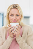 Beautiful young woman with coffee cup in kitchen Royalty Free Stock Image