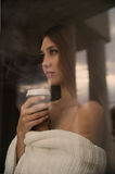 Beautiful young woman with coffee cup looking through the window. Sunrise, sunset Royalty Free Stock Image