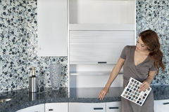 Beautiful young woman with color samples looking at contemporary kitchen cabinets Royalty Free Stock Photography