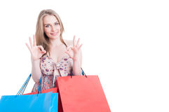 Beautiful young woman with colored gift bags doing ok gesture. Beautiful young woman with colored gift bags after shopping doing ok gesture with both hands Stock Photo